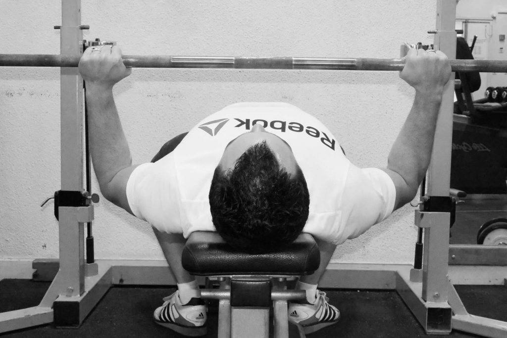 Développé couché : les coudes sont plus rapprochés mais toujours sous la barre = moins exigeant pour les triceps.